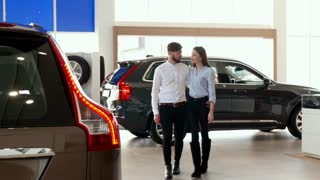 Young couple walking at the car dealership. Handsome brunette guy and his girlfriend looking at the one of cars at the showroom. Caucasian bearded man and brown haired woman standing against