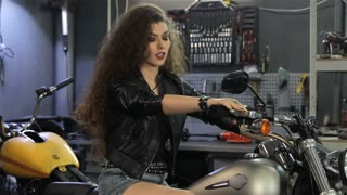 Young female biker showing her thumb up on the motorcycle. Pretty curly woman in black leather jacket examining motorcycle. Attractive caucasian girl approving chopper at the motorcycle workshop