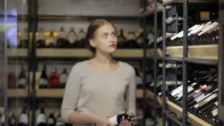 Young female deciding which wine to buy