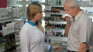 Young female druggist giving client lozenges for cough at the pharmacy. Senior caucasian man taking blister of lozenges from the hands of pretty blond woman in medical uniform. Aged male customer and