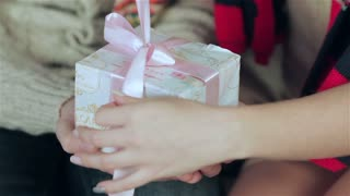 Young handsome guy holding hands while his darling gift unleashes a gift