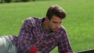 Young handsome man lying on grass