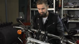 Young male biker examining the chopper at the motorcycle workshop. Bearded caucasian man leaning on the handlebar of motorcycle. Attractive man in black leather jacket looking into the camera while