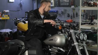 Young male biker posing on the classic chopper at the motorcycle workshop. Cool bearded man folding his arms on his chest. Attractive caucasian man in black leather jacket toching different parts on