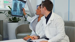 Young male doctor pointing his hand on the x-ray at the hospital. Attractive african american woman in white coat holding x-ray in her hand. Brunette caucasian medical specialist describe x-ray image