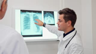 Young male doctor showing something on x-ray to his elder colleague. Senior gray man in white coat standing backwards the camera. Brunette caucasian man moving his hand on the x-ray image