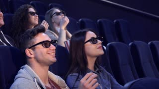 Young people in 3D viewers laughing at the movie theater. Caucasian brunette girl touching her hair at the cinema. Asian girl taking flake of popcorn from the bucket of caucasian guy