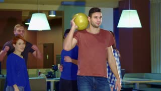 Young people raising their hands at the bowling. Brunette caucasian guy rolling the ball against background of his friends. Attractive male bowler celebrating successful release