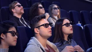 Young people watching 3D film at the movie theater. Blond guy pointing his hand on the screen at the cinema. Asian girl in 3D viewers slightly bending over on the seat