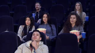 Young people watching movie at the movie theater. Two boys and four girls sitting on different rows at the cinema. Asian teenage girl talking to caucasian girl