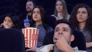 Young people watching serious film at the movie theater. Teenagers having sad faces while watching some dramatical moments. Curly caucasian girl raising her hand to her mouth