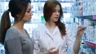 Young pharmacist helping customer