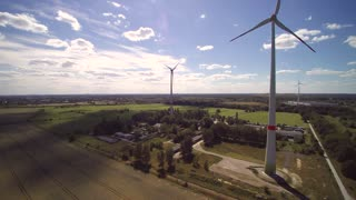 Aerial view of wind farm turbines moving