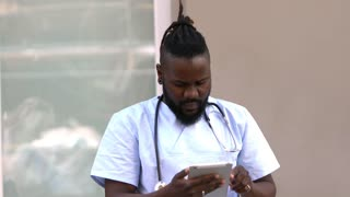 African american male doctor checking medical documents on tablet computer