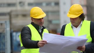 Architect giving a colleague arrangements about a new construction site. Outdoors