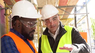 Architect wearing yellow safety vest and goggles providing instructions to a colleague with orange vest and tablet on the construction site