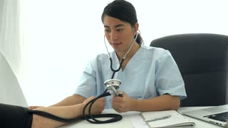 Asian female doctor sitting at desk measuring blood pressure