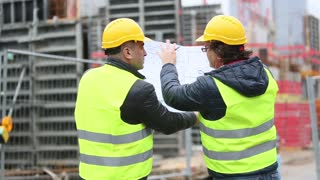 Back turned engineer and technician at construction site reviewing office blueprints and technical drawings