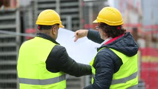 Back turned technician and architect at construction site reviewing office blueprints and technical drawings