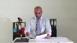 Bald bureaucrat sitting at desk in office stamping paperworks