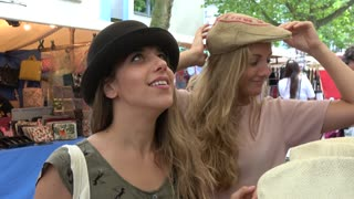 Blonde girls trying on hats at market stall