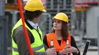 Break at work on construction site: male and female engineers with safety jacket and yellow helmets drinking beer