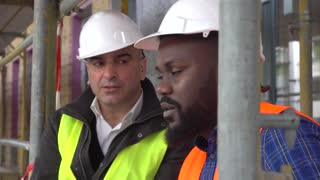 Close up of two engineers, a black and a white with helmets, discussing and sitting among scaffolding