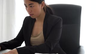 Concentrated asian girl working at computer and taking notes