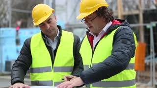 Construction site manager showing and explaining office blueprints pointing at something