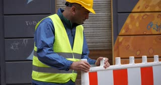 Construction worker wearing safety jacket and yellow hardhat moving a safety barrier on construction site
