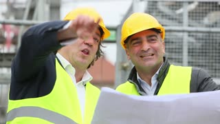 Construction workers laughing reading office blueprints