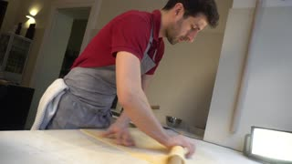 Cook uses a rolling pin to create a round piece of dough