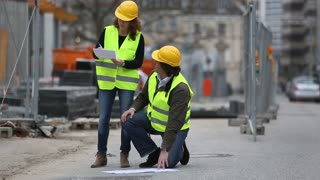 Crouched engineer checking blueprints with a female colleague on construction site