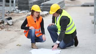 Crouched male and female engineers looking at office blueprints