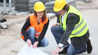 Crouched male and female engineers talking on a construction site