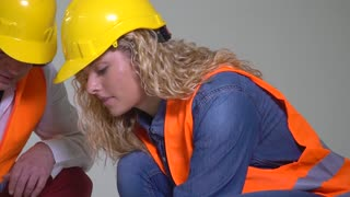 Crouched male and female engineers working together