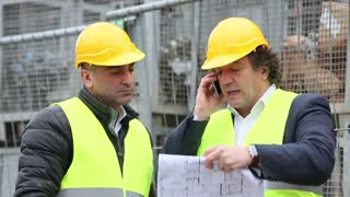 Engineer at telephone and another construction manager discussing office blueprints and drawings
