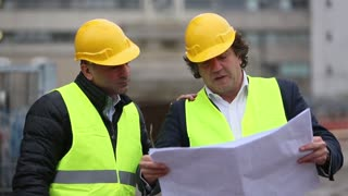 Engineer giving a colleague arrangements about a new construction site