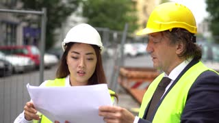 Engineer with female Asian colleague working at construction site