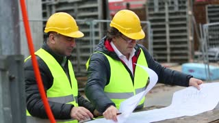 Engineers checking office blueprints pointing at something on a construction site