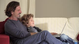 Father and son using laptop sitting on the couch