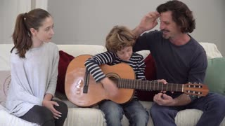 Father teaching his son and daughter how to play guitar