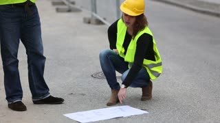 Female crouched engineer talking with a male colleague on a construction site