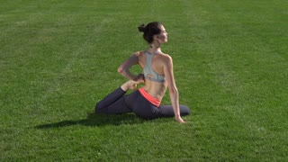 Fit girl doing yoga and stretching in park