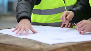 Hands of construction personnel with drawings