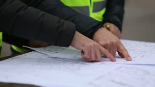 Hands of construction personnel with office blueprints