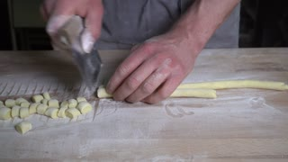 Human hands cutting rolled dough into little shapes