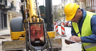 Left-handed mechanical engineer wearing safety jacket and yellow hardhat checking excavator and taking notes