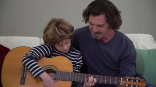Loving father showing his little son how to play guitar