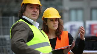 Male and female construction workers checking the site comparing data on a laptop